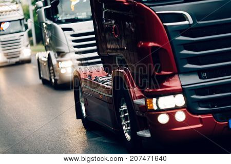 Trucks being driven on road picking up goods