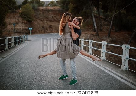 Man holding her girlfriend by the arms in the middle of a road