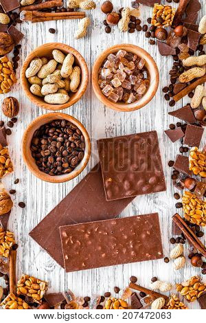 Chocolate bars of different varietes on grey wooden background top view.