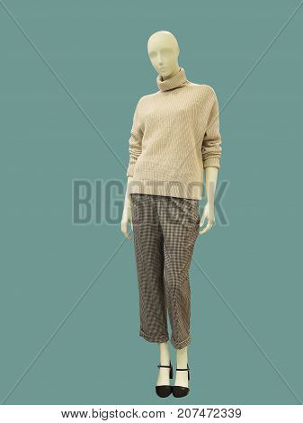 Full-length female mannequin dressed in sweater and trousers isolated on green background. No brand names or copyright objects.
