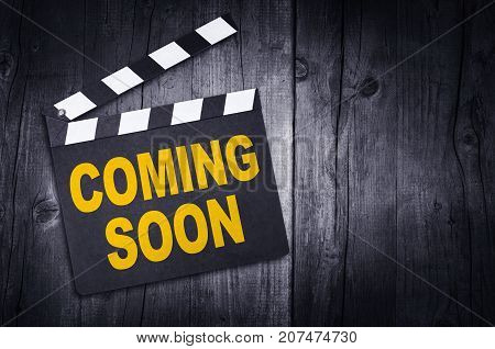 Coming soon movie clapper board on wooden background