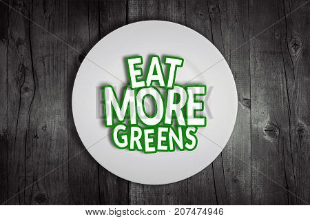 Eat more greens plate on wooden table background