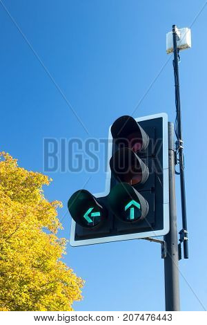 Green go arrows on British traffic lights. Signal for left turn and straight ahead. Highway code sign.