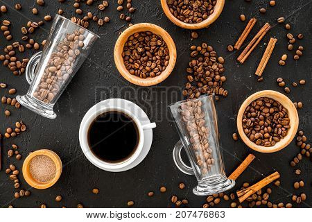 Cup of black coffee near coffee beans on black background top view.