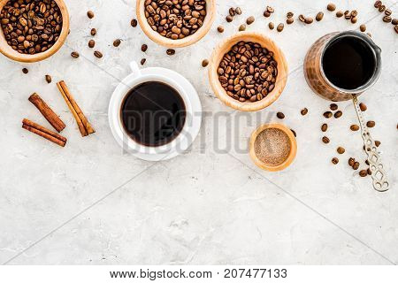Cup of black coffee near coffee beans and cinnamon on grey background top view.