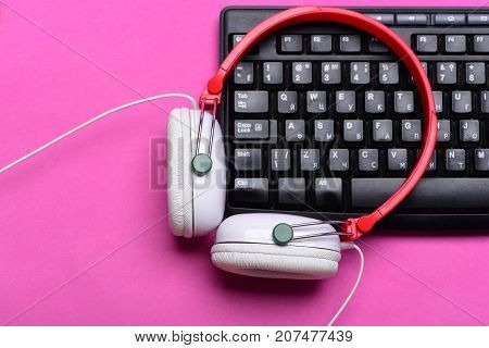 Electronic appliances on pink background. Earphones in red and white colors with computer keyboard. Sound recording and technology. Music and digital equipment concept. Headphones and black keyboard