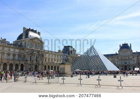 PARIS, FRANCE - JUNE 5, 2017: Louvre Museum and Pyramid Main Entrance with Tourists in front. World largest museum and central city landmark. Famous cultural attraction in Paris, attracts many people