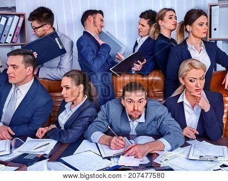 Business people office. Team people are unhappy with their leader. Intern man manager littered with work and does not cope with his duties. Employees do not want to obey new boss