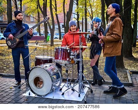 Festival music band. Friends playing on percussion instruments in city park. Fountain and trees in the background. Ordinary people earn a living by concerts. Girl with blue hair.