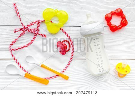 bottle with breastmilk and infant formula powdered healthy food, toys and bib on white wooden desk background top view