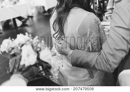 Her husband gently hugs a woman tenderly