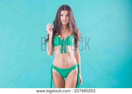 Beautiful young woman in green swimwear on the green background