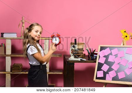 Kid and school supplies on pink background. Schoolgirl with happy face stands near bookshelf desk and blackboard with pink stickers. Girl holds red alarm clock. Back to school and study time concept