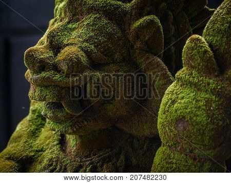 Balinese Carved Stone Statue of Rakasa covered with green moss. at Hindu Temple.