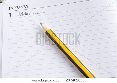 Pencil on a calendar with the page showing the first day of the year in a setting goals concept