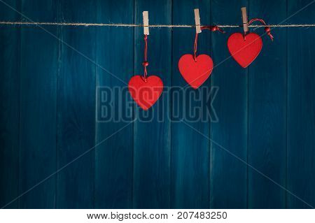 Red wooden hearts on the twine with clothespins on blue wooden background. Valentine's Day cards with copy space. Romance love concept.