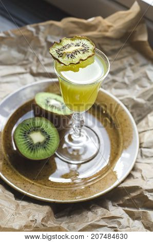 Cocktail with kiwi slice in a glass on a plate brown paper background. Green drink selective focus. Healthy concept