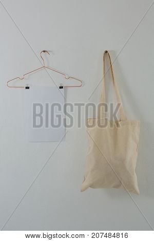 Close-up of paper and bag hanging against white wall