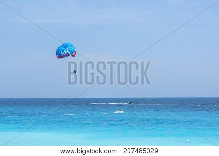 NICE COTE D'AZUR, FRANCE - JUNE 27,2017: Beautiful daylight view to blue sea. People walking on beach and parachute man cruising in air.
