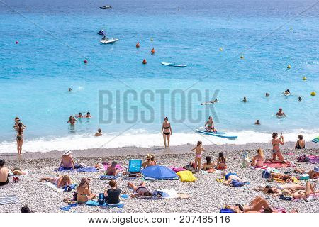 NICE COTE D'AZUR, FRANCE - JUNE 27,2017: Beautiful daylight view to city beach. Blue water with people walking on sand.