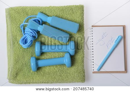 Dumbbells And Skipping Rope Lie On Towel On White Background