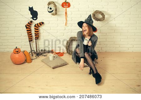 Halloween woman in witch hat winking with cups. Happy holiday celebration concept. Girl sitting on wooden floor. Coffee or tea break. Pumpkins wreaths mummy symbols and decorations on brick wall.