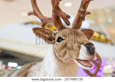 Close-up detail of a life sized reindeer plush doll at a department store during Christmas. Holidays and Xmas concept.