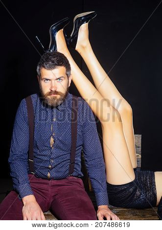 Legs of woman in shoes at man with beard. Guy at table with female legs. Man in shirt isolated on black background. Love and relations dominating. Romance and couple in love.