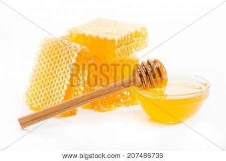 Honeycomb and  bowl with honey and  wooden dipper on a white background
