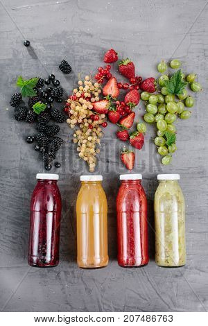 Top view of a bottle with vitamin fresh juices and pour berries on wooden background