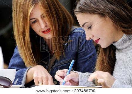 Attractive women are signing an agreement in an outdoor cafe. Lifestyle concept.