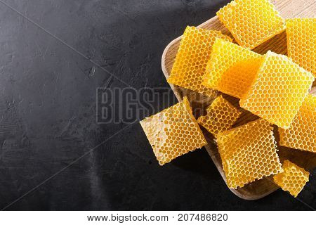 Top view of a piece of honeycomb with honey on a wooden board on a dark background. copy space