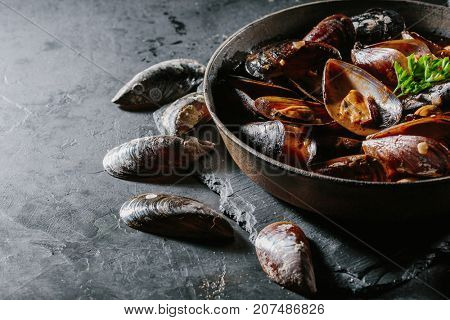 Freshly cooked mussels in a tomato sauce in a frying pan on a dark stone background. Copy space.