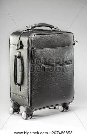 Black suitcase for traveling on wheels on a gray background