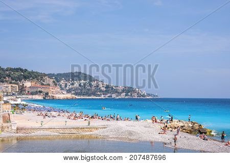 NICE COTE D'AZUR, FRANCE - JUNE 27, 2017: Beautiful daylight view. Blue water with people walking on sand, people fishing.