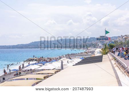NICE COTE D'AZUR, FRANCE - JUNE 27, 2017: Beautiful daylight view to resort of Nice. Beach full of white umbrellas and people.