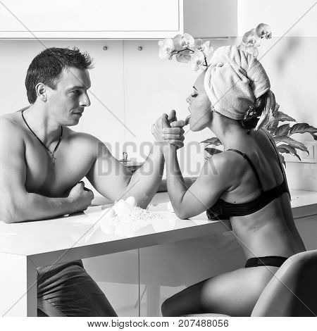Young sexy family couple of attractive undressed woman in black lingerie and terry towel turban on head having arm wrestling with handsome muscular man with bare chest sitting in kitchen square