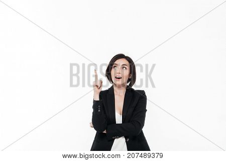 Portrait of a happy excited businesswoman in a suit pointing finger up at copy space isolated over white background