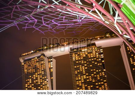 January 4 2017. Wide angle aerial view of the Marina Bay Sands Hotel with the Supertree Grove in the foreground glowing with window lights at night. Singapore. Travel and vacation editoral concept.