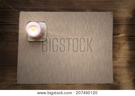Candle on the wooden table with copy space top view.