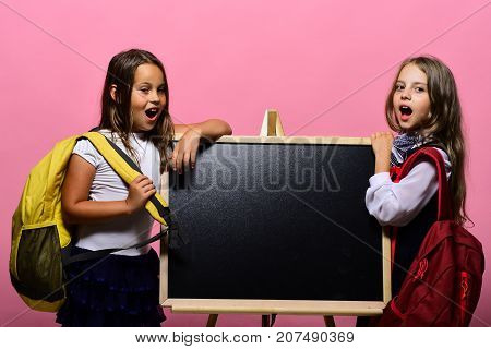Kids Wearing Schoolbags Lean On Shiny Blackboard, Copy Space