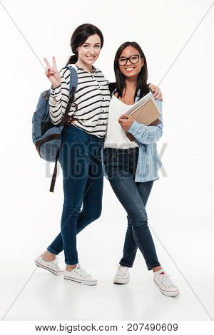 Couple of two happy multiethnic female students with backpack and books standing and looking at camera isolated over white background