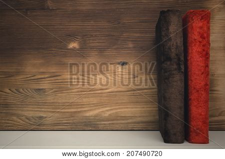 Old vintage books on the bookshelf on wooden wall background with copy space.