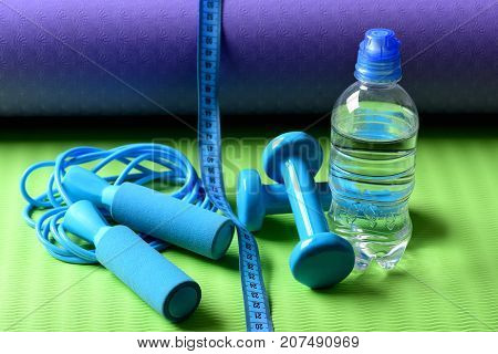 Workout And Refreshment Concept. Bottle Or Water Near Jump Rope