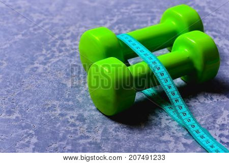 Dumbbells In Green Color And Cyan Measuring Tape Around Them