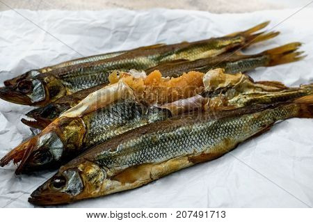 Delicious smoked fish smelt osmerus caviar lying on light-colored paper on a wooden background. The horizontal frame.