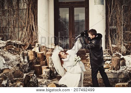A Man Attacks An Icicle On A Woman In A White Fur Coat In A Snow Park Against A Building Background
