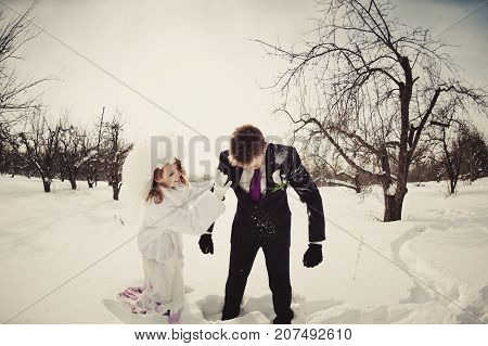 A Beautiful Ginger Bride In A White Fur Coat Shakes The Snow From The Groom's Costume In The Park. W