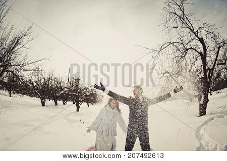 A Beautiful Ginger Bride In A White Fur Coat And Groom Throw Snow In The Park. Winter Wedding Outdoo