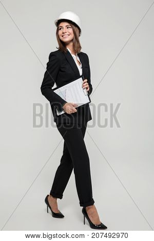 Full length portrait of a happy young woman in hard hat and suit looking away at copy space while walking and holding clipboard with documents isolated over white background